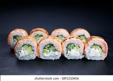 Grilled salmon sushi rolls served on slate, food background. Japanese restaurant menu photo, seafood, Japanese food.