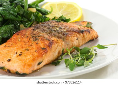 grilled salmon with thyme, lemon and spinach on a white plate, homemade vegetarian low carb dish, close up with selected focus, narrow depth of field