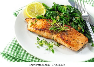 grilled salmon with thyme, lemon and spinach on a plate, vegetarian low carb dish, green napkin on a white background, selected focus, narrow depth of field