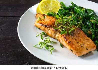 grilled salmon with thyme, lemon and spinach on a white plate on a dark rustic wooden table, homemade vegetarian low carb dish, close up with selected focus, narrow depth of field
