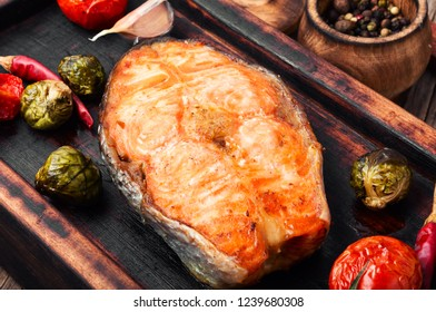 Grilled salmon with tomato, pepper and cabbage.Fish steak with vegetable garnish.Grilled fresh fish.Beautiful festive dish