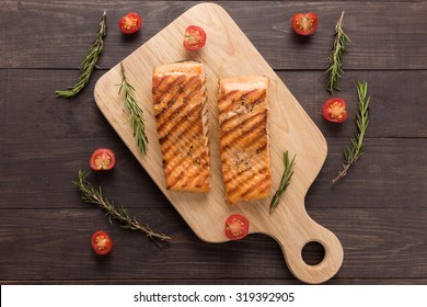 Grilled salmon and tomato, rosemary on the wooden background.