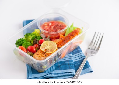 Grilled salmon with tomato salsa and salad cooked by clean food concept in lunch box