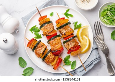 Grilled salmon and vegetables skewers on white plate, top view