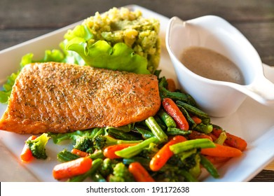 Grilled salmon/trout fillet with potato-spinach mash and vegetables. Indoors closeup.