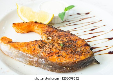 Grilled salomon steak with lemon on white background