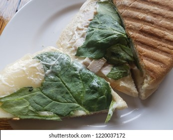 grilled sandwich with cheese, ham, and spinach on a while plate on a table