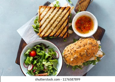 Grilled sandwich  with chicken, arugula on wooden cutting board with salad and sauce top view on blue background. Nutritious and healthy breakfast