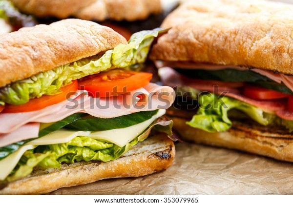 Grilled Sandwich with lettuce, slices of fresh tomatoes, cucumber, red onion, salami, ham and cheese