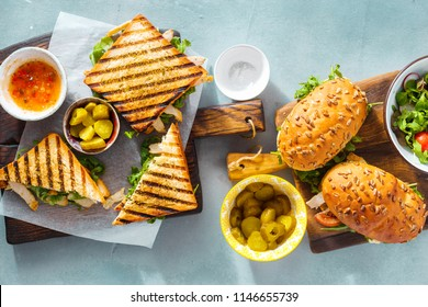 Grilled sandwich with nuggets, salad, sauce and pickled cucumbers on blue background top view. Various snacks. Outdoor food concept