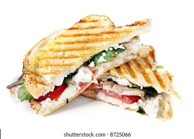 Grilled sandwich or panini.  With goat's cheese, spinach, tomatoes and mushrooms.  Delicious vegetarian lunch.  Isolated on white.