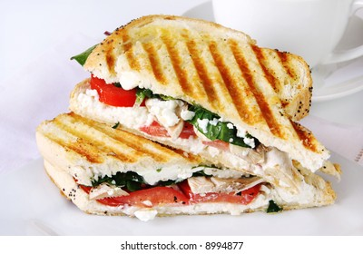 Grilled sandwich or panini, with goat's cheese, spinache and tomatoes.  Cup of coffee behind.