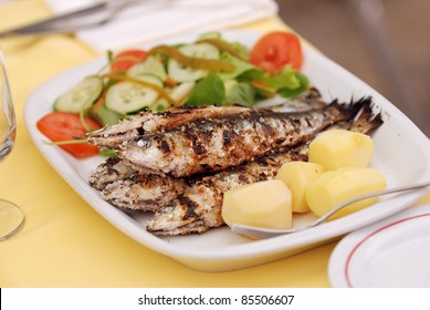 Grilled sardine with potato and salad