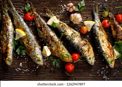 Grilled sardines with addition of fresh  herbs, lemon and spices on a wooden background. Grilled seafood, barbecue
