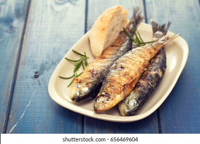 grilled sardines with bread on dish