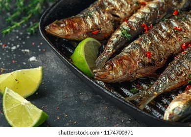 Grilled sardines with thyme, chili and lime wedges on cast iron skillet.