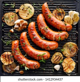 Grilled sausage with the addition of herbs and vegetables on the grill plate, outdoors. Grilling food, bbq, barbecue