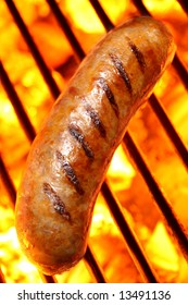Grilled sausage or hot dog on a fire hot barbecue grill.