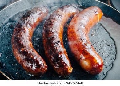 Grilled sausage on hot barbecue dish