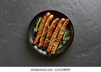 Grilled sausage on plate over black stone background with copy space. Top view, flat lay