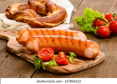 Grilled sausage with vegetables and mostard on wooden board