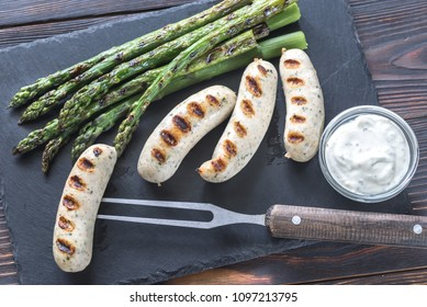 Grilled sausages with asparagus and creamy garlic sauce