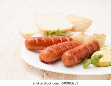 Grilled sausages with baked vegetables on the plate next to the buns with sesame seeds on a white wooden table. Background image.