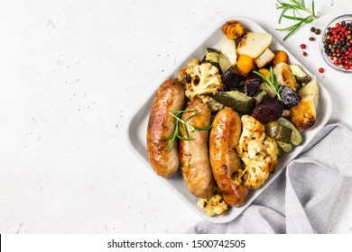 Grilled sausages with baked zucchini, potatoes, beets and cauliflower. Top view, space for text.