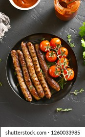 Grilled sausages and cherry tomatoes on plate over black stone table. Top view, flat lay