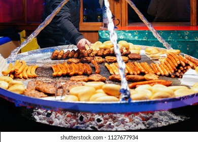 Grilled sausages at Christmas Market at Town Hall in Winter Berlin, Germany. Advent Fair Decoration and Stalls with Crafts Items on the Bazaar.