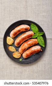 Grilled sausages in frying pan, top view