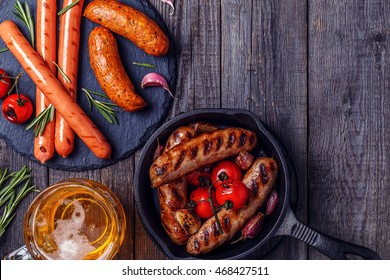 Grilled sausages with glass of beer on wooden table. Top view with copy space.