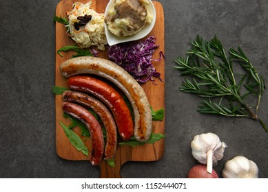 Grilled sausages with mash potatoes on wooden board