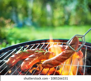 Grilled sausages on grill with smoke and flame on a meadow. Barbecue picnic