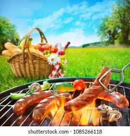 Grilled sausages on grill und picnic basket on a meadow