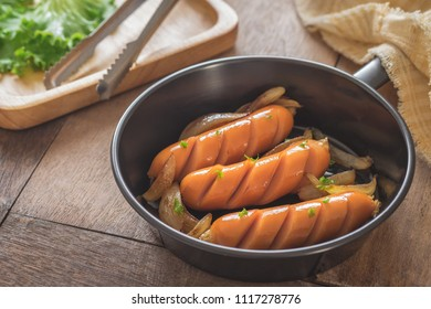 Grilled sausages with onion in frying pan