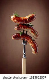 Grilled sausages with rosemary. Hot sausages on a fork sprinkled with rosemary.