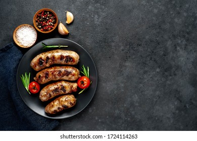 grilled sausages with spices and rosemary in a black plate on a stone background with copy space for your text