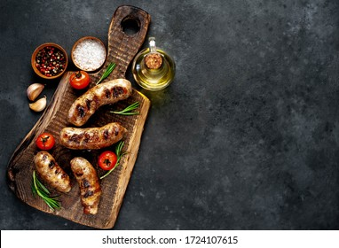 grilled sausages with spices and rosemary on cutting board on stone background with copy space for your text