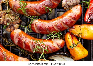 Grilled sausages and vegetables with addition spices and fresh herbs, top view