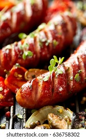 Grilled sausages and vegetables with addition spices and fresh herbs on a grill, close up