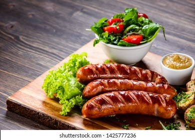 Grilled sausages and vegetables on cutting board