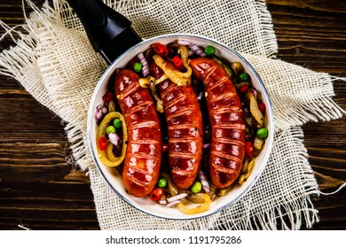 Grilled sausages with vegetables in pan on wooden table