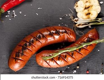 Grilled sausages with vegetables and spices on black background
