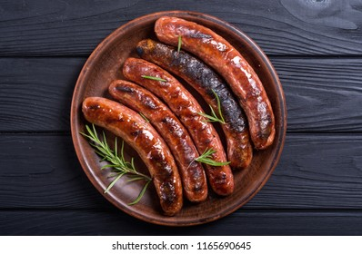 Grilled sauusages on a plate . Unhealthy food background . Barbecue