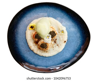 Grilled scallops with caviar and molecular froth on blue clay plate isolated on white background