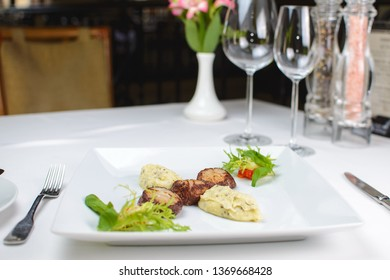grilled scallops with celery puree and vegetables. on a white plate