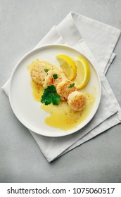 Grilled scallops with lemon on white plate