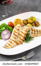 Grilled sea bass fillet with salad and potatoes on stone table