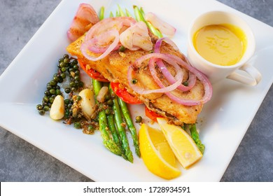 Grilled sea bass fish meat steak with vegetable and lemon
